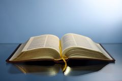 Opened Bible with gold letters with a leather cover reflected on a glass table.  royalty free stock image