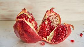 Opened big red pomegranate with seeds on the white concrete bckground. Sliced fresh pomegranate on the light wooden background Stock Photography