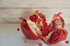 Opened big red pomegranate with seeds on the white concrete surface. Sliced juice pomegranate on the light background Royalty Free Stock Images