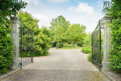 Opened black wrought iron gate of a large estate Stock Photography