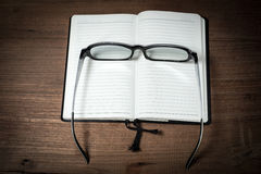 Opened blank notebook with eyeglass on wooden Royalty Free Stock Photo