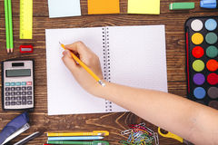 Opened blank notebook, hand with a brushwith frame of school sup Royalty Free Stock Photos