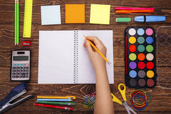 Opened blank notebook, hand with a brushwith frame of school sup Royalty Free Stock Photography