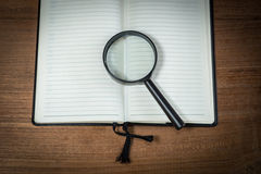 Opened blank notebook with Magnifying Glass Royalty Free Stock Photography
