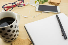 Opened blank notebook with pen, smartphone and cup of coffee and cookies Royalty Free Stock Photos