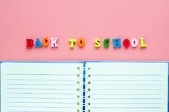 Opened blank notebook with wooden text BACK TO SCHOOL on pink ba stock photo