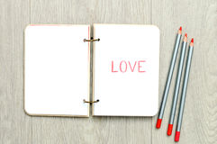 Opened blank notepad with drawn word LOVE on wooden table Royalty Free Stock Photos