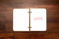 Opened blank notepad with drawn word LOVE on wooden table. Valentine`s Day greeting card Royalty Free Stock Photography