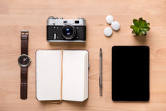 Opened blank notepad, pen, watch, vintage camera, tablet and flower Royalty Free Stock Photography