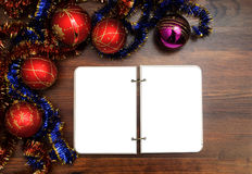 Opened blank notepad on a table with a Christmas decoration Stock Photos