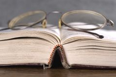 Opened Book. Closeup image of opened book with reading glasses stock photos