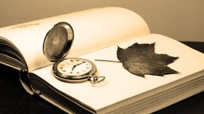 Opened book. Pocket watch and autumn leaf on the opened book, sepia tone Stock Photo