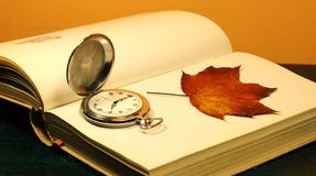 Opened book. Pocket watch and autumn leaf on the opened book Stock Image