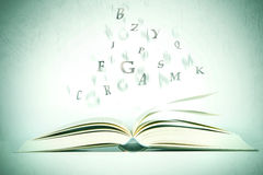 Opened book with alphabet letter flying out of pages Royalty Free Stock Image