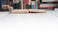 Opened book background. On a wooden table Stock Photos