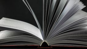 Opened book on black background. The pages swaying slightly. Opened book on black background. The pages swaying slightly stock video