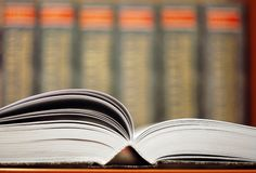 Opened book with bookshelf background Stock Photography
