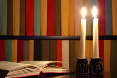 Opened Book, Candles And Bookshelves Stock Photo