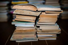 Opened book on columns of books, shallow depth of field,. Cracked wood floor royalty free stock image