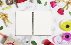 Opened book with empty white paper on white marble desk with Christmas and Valentines decorations Royalty Free Stock Images
