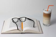 Opened book et glass of Latte Macchiato Royalty Free Stock Image
