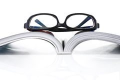 Opened book with eye glasses Stock Photography