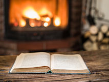 Opened book and fireplace with warm fire on the. Opened book on the wooden table. Fireplace with warm fire on the background Stock Image