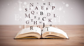 Opened book with flying letters Royalty Free Stock Image
