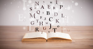 Opened book with flying letters Stock Images