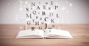 Opened book with flying letters Stock Image