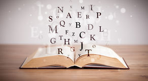 Opened book with flying letters Royalty Free Stock Images