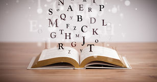 Opened book with flying letters Royalty Free Stock Photography
