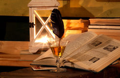Opened book, glass, feather, lamp. Opened book, background with books, glass with feather, lamp (lantern royalty free stock image