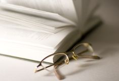 Opened book and glasses Stock Images