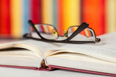 Opened book and glasses on colored background Stock Image