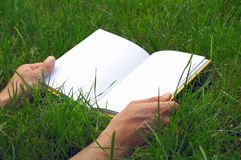 Opened book on the grass Royalty Free Stock Photos