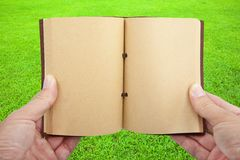 Opened book in hand  on the grass Stock Photography