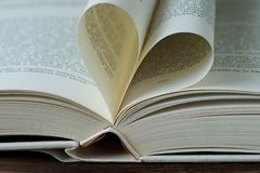 Opened book with heart shaped page Royalty Free Stock Photo