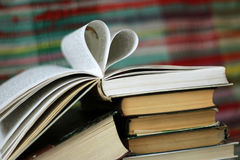 Opened book with heart shaped pages on colourful background Royalty Free Stock Photos