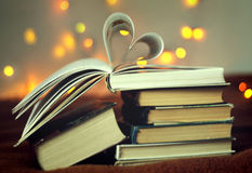 Opened book with heart shaped pages with lights glowing background Stock Photos