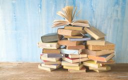 Opened book on a large pile of books, reading education,literature. Good copy space royalty free stock image