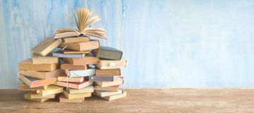 Opened book on a large pile of books, reading education,literature. Good copy space royalty free stock images
