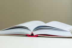 Opened Book. Lay on white table Royalty Free Stock Photography