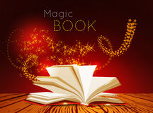 Opened book with magic light. Stock Photos