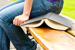 Opened book next to a woman sitting on a bench Royalty Free Stock Photos