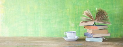 Opened book on a pile of books and a cup of coffee, panorama, reading, literature, copy space. Opened book on a pile of books and a cup of coffee, panorama stock image