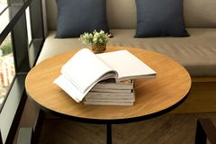 Opened book and plant on wooden table. Indoor Stock Image