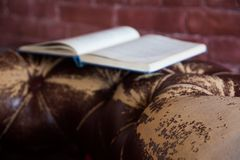 Opened book on a vintage leather sofa. Brick wall background Stock Images