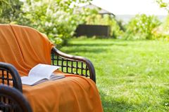 Opened book on wicker chair in the garden stock photos