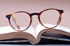 Free Opened Book With Reading Glasses Stock Images - 164152054